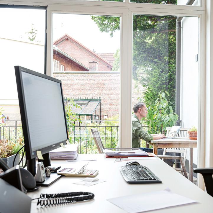 Blick aus Büro auf den Balkon. Im Hintergrund sitzt Wolfgang Wiese vor einem Notebook.